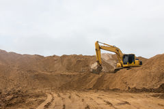 Backhoe on the sand track. Royalty Free Stock Images