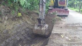 Backhoe som gräver gropen på sidan av vägen lager videofilmer