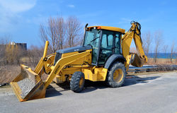 Backhoe on street. A yellow backhoe sitting on the street in Stoney Creek, Ontario close to the lake Ontario, on a beautiful sunny day in early spring stock image
