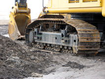 Backhoe Track and Bucket. This is a view of the left-hand side of a backhoe, showing only the track and the bucket next to a pile of dirt Stock Images