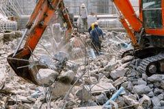 Backhoe utrzymania betonu gruzy opuszcza w budowa terenie Zdjęcia Royalty Free