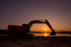 Backhoe was digging earthmoving work. At construction site on sunset background stock image