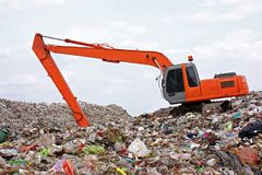 Backhoe working on garbage dump in landfill stock photos