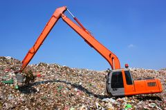 Backhoe working on garbage dump in landfill stock image