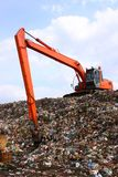 Backhoe working on garbage dump in landfill royalty free stock photos