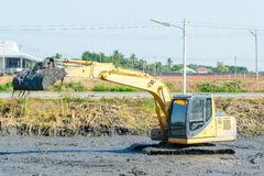 Backhoe working in mud swamp Royalty Free Stock Image