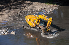 Backhoe working in a river Stock Image