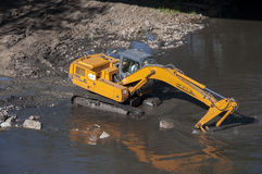 Backhoe working in a river Stock Photos