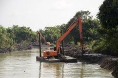 BackHoegrävskopamaskin som muddrar kanalen på förbudPak Pra fiske Arkivfoton