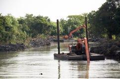 BackHoegrävskopamaskin som muddrar kanalen på förbudPak Pra fiske Royaltyfria Foton