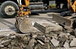 Backhoehinken lyfter upp stora bitar av betong Arkivbilder
