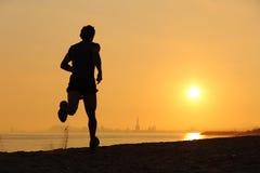 Backlight человека бежать на пляже на заходе солнца Стоковые Фотографии RF