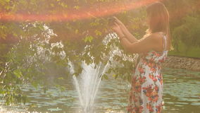 Backlight Backside Blond Girl Photos Fountain in Pond. At backlight backside view blond girl in colorful frock takes photo of fountain in pond behind tree in stock video