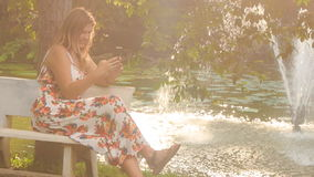 Backlight Blond Girl Sits on Bench at Fountain Plays Iphone. At backlight blond girl in colorful frock sits on bench near pond with fountain in park smiles and stock footage