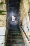 Backlight com reflexões do sol em escadas de pedra antigas sob um túnel em um corredor estreito ao lado dos bancos do rio de Dour foto de stock royalty free