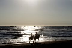 couple on horseback for romantic walk on the beach stock images