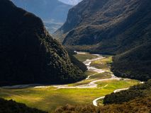 Mountain river and meadow in the steep Routeburn flats valley reflecting the sun stock images