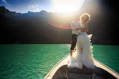 backlight groom blonde bride in fluffy on nose of longtail boat Royalty Free Stock Image