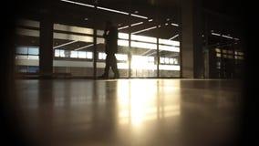 Backlight la siluetta dell'uomo che cammina davanti alla grande finestra video d archivio