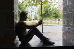 Backlight of man with tablet computer sitting in the street. Royalty Free Stock Image