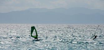 Backlight seascape med konturn av att vindsurfa för två personer Royaltyfri Foto