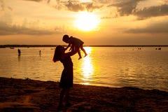 Backlight Seitenansichtporträt einer glücklichen Mutter, die ihren Kindersohn bei Sonnenuntergang aufzieht stockfoto