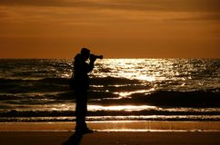 Backlight silhouette of photographer standing upon the foreshore Stock Photography