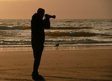 Backlight silhouette of photographer standing upon the foreshore Royalty Free Stock Photography