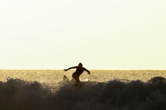 Backlight Silhouette Surfer. In the Ocean at Sunset Stock Photo