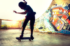 Backlight skater making a trick with His skate with friends Royalty Free Stock Image