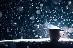 Backlighted cup of hot coffee on night snowy background; Stock Photos