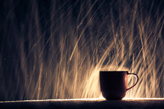 Backlighted cup of hot coffee on night snowy background; Stock Photography