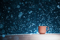 Backlighted cup of hot coffee on night snowy background; Stock Images