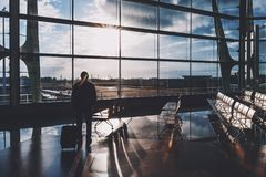 Silhouette male tourist indoors of airport terminal. Backlighted silhouette of man traveler with his luggage standing alone next to giant windows inside of Royalty Free Stock Photos