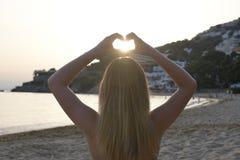 Backlighting Bild eines Mädchens in einer Yogaposition zurück zu der Kamera, die eine Herzform mit ihren Händen macht stockfotos