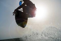 Backlighting eines Surfers, der bei Sonnenuntergang springt stockfotografie