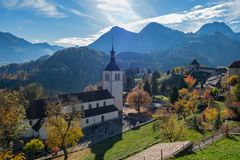 Backlightmening met de herfstlicht op de alpen, de kerk en de begraafplaats in Gruyeres, Zwitserland royalty-vrije stock afbeelding