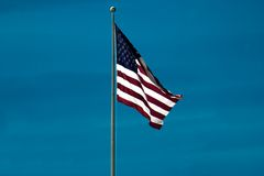 Backlit American Flag. An American flag waving in the night sky and being backlit by stadium lights Stock Image