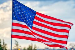 A backlit American flag waving in the breeze. stock images