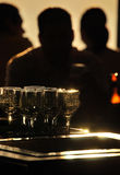 Backlit bar scene. A backlit bar scene with patrons and glasses Stock Image