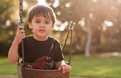 Backlit boy on swing. An adorable, multicultural, Asian and Caucasian, 2 and a half year old boy is on a swing at the park. Portrait is backlit by the sun. Boy royalty free stock images