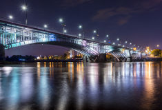 Backlit bridge at night and reflected in the water Stock Photography