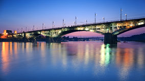 Backlit bridge at night and reflected in the water Royalty Free Stock Photos