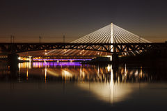 Backlit bridge at night and reflected in the water Stock Photo