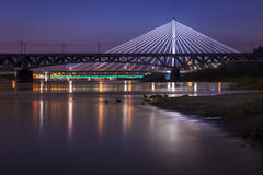 Backlit bridge at night and reflected in the water Stock Image