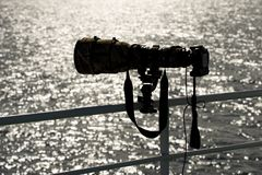 Backlit camera with long lens on railing Stock Image