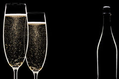 Backlit champagne flutes. Silhouette of two glasses of champagne with bottle Stock Photos