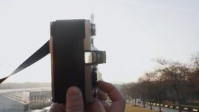 Backlit close-up shot, hand holding vintage film camera, sunset Paris Eiffel Tower is seen in viewfinder slow motion.