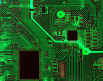 Backlit Computer Circuit Board Background. Detail of a computer circuit board with chips back lit from behind as an electronic background Royalty Free Stock Images