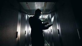 Backlit computeringenieur werkt in de serverruimte stock videobeelden